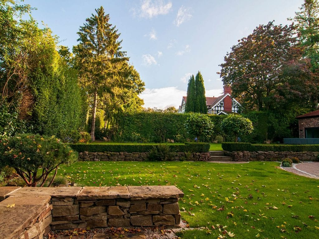 dry stone wall seating which is backdropped by an existing stone wall and clipped hedges and perennial border