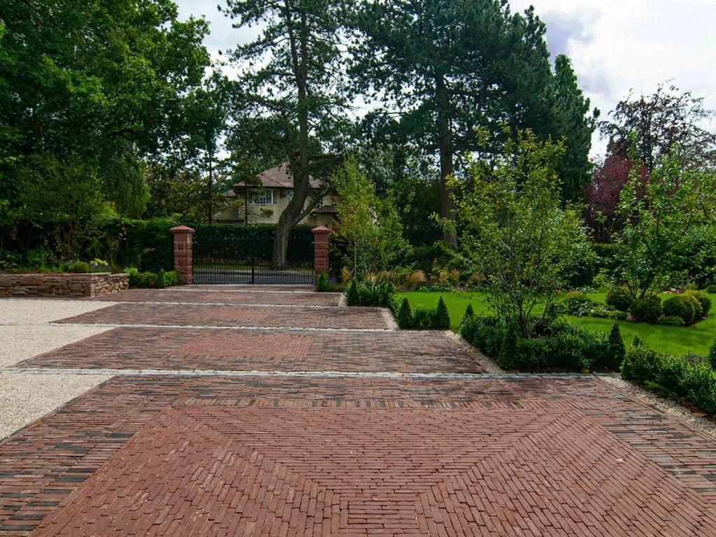 long front drive and frontage area paved in Flemish style clay bricks with large gravel area for parking and large front lawn in front of house