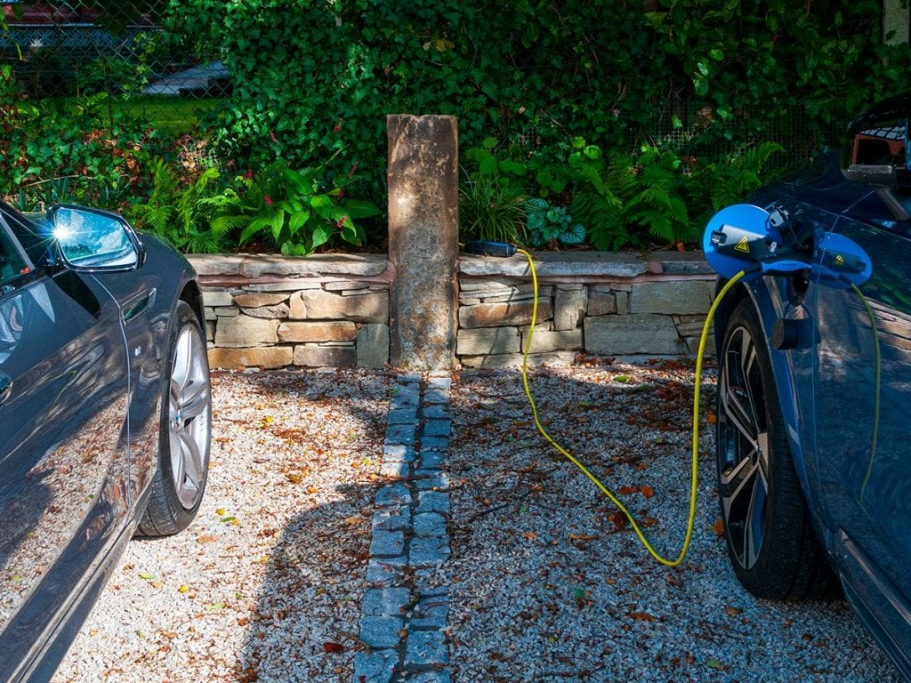 reclaimed sandstone gate post with electric charging point for volvo set within sandstone wall around driveway