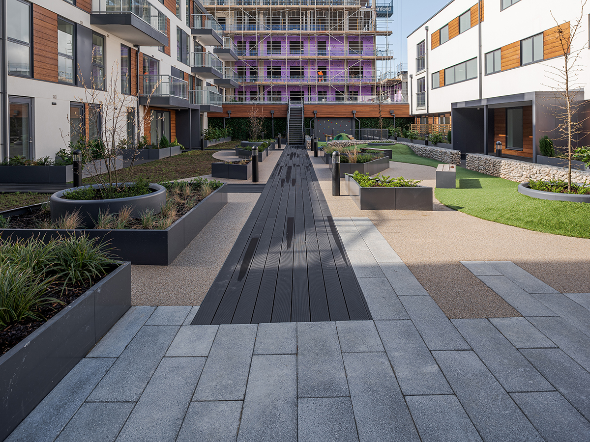 Central axis boardwalk through roof gardens with raised curving planters containing grasses and trees surrounded by gabion wall designed by Natural Dimensions