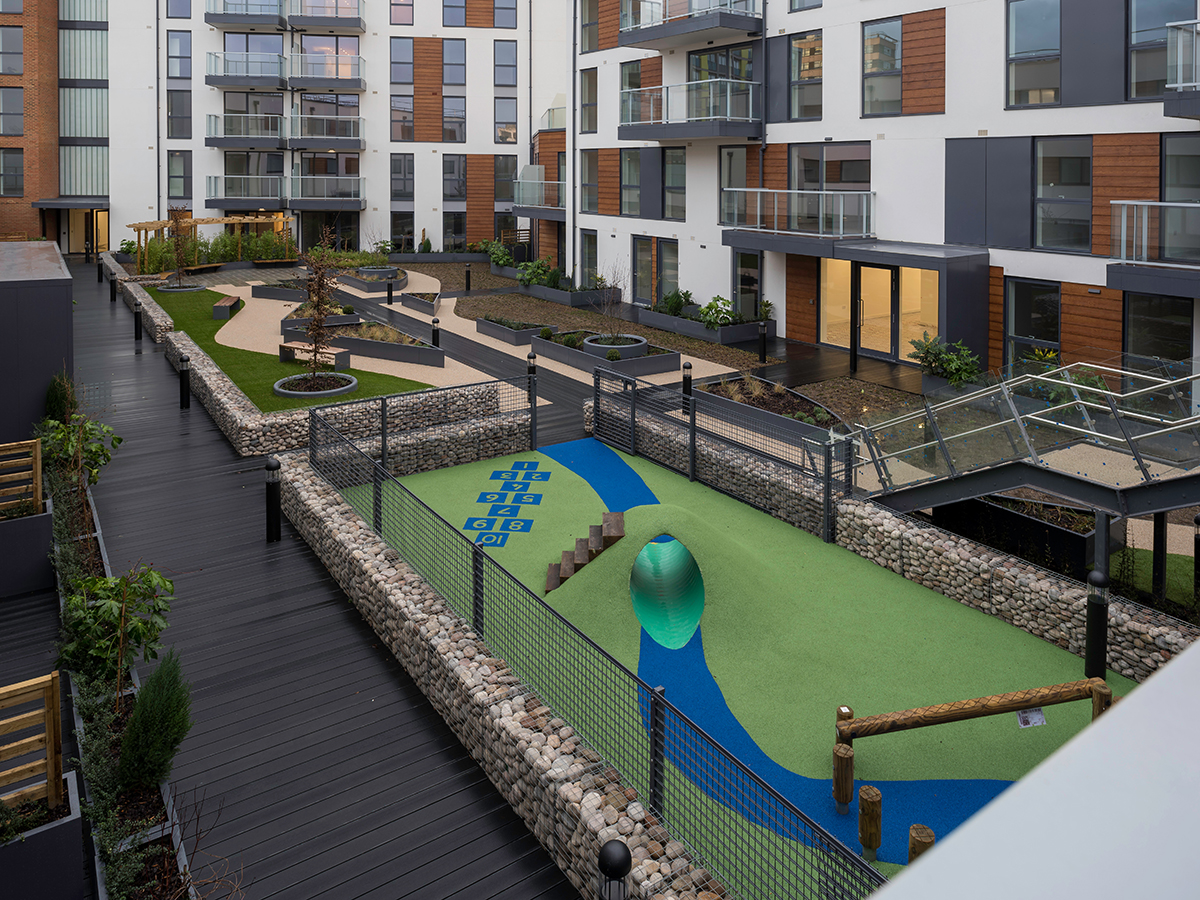 Roof garden play area surrounded by gabion wall and weldmesh fencing and raised planting beds and mounded artificial turf