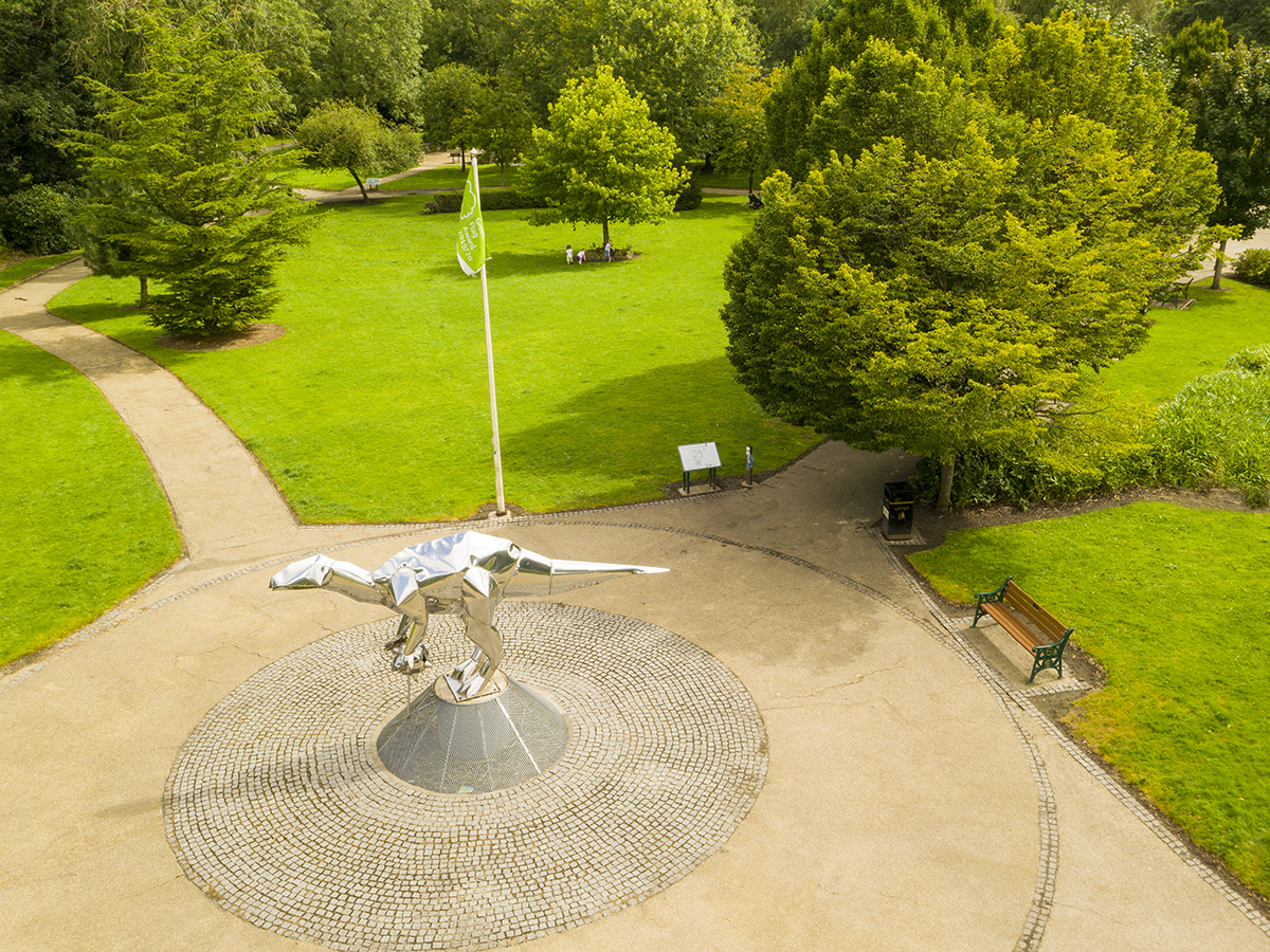 aerial view of close park frontage and park green with dinosaur sculpture