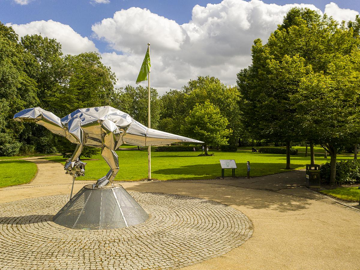 stainless steel dinosaur sculpture in close park within granite sett circle