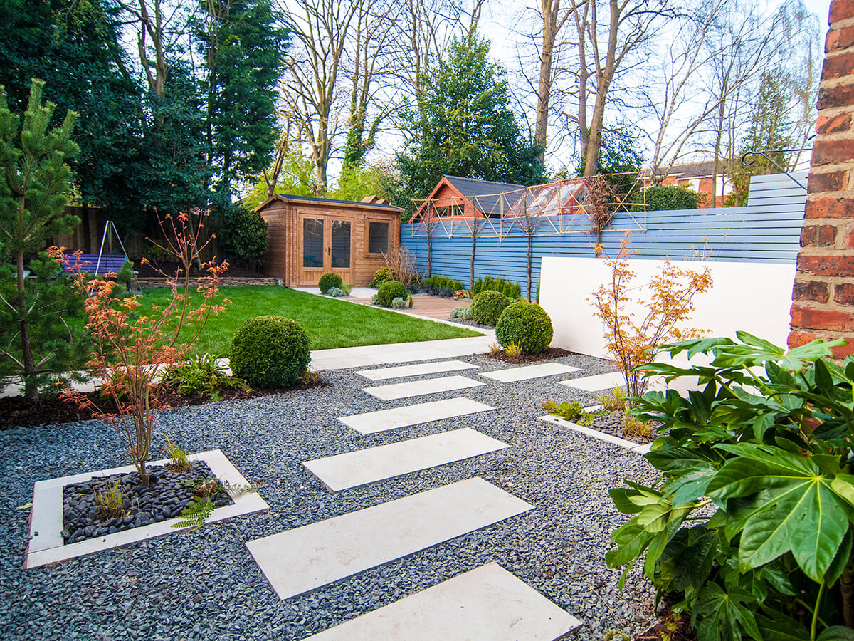 Private residence Heaton Moor view of stepping stones through contemporary Japanese garden with black basalt gravel, acer katsura, fatsia, Chinese black pebbles, box balls, topiary, Little Greene Juniper Ash, pine tree, pleached hornbeam, white rendered wall, dunster summer house.