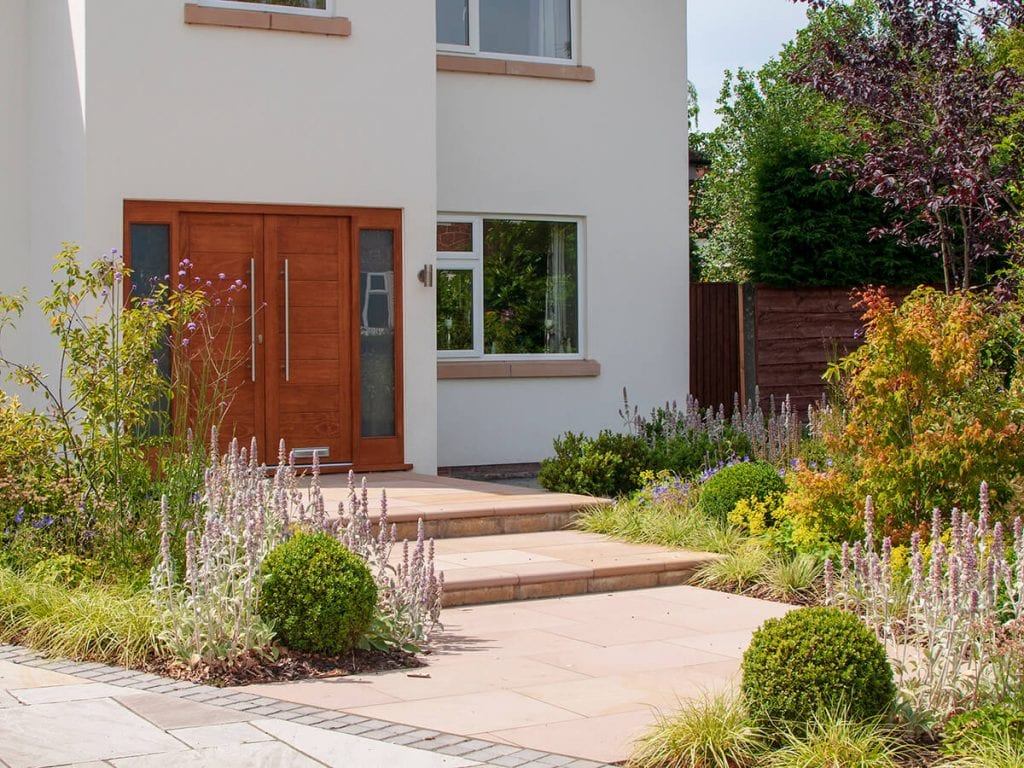 View of front garden designed by Natural Dimensions rising to front door including Carex Evergold, Astrantia, verbena boniarensis , Heuchera, stachys and buxus balls