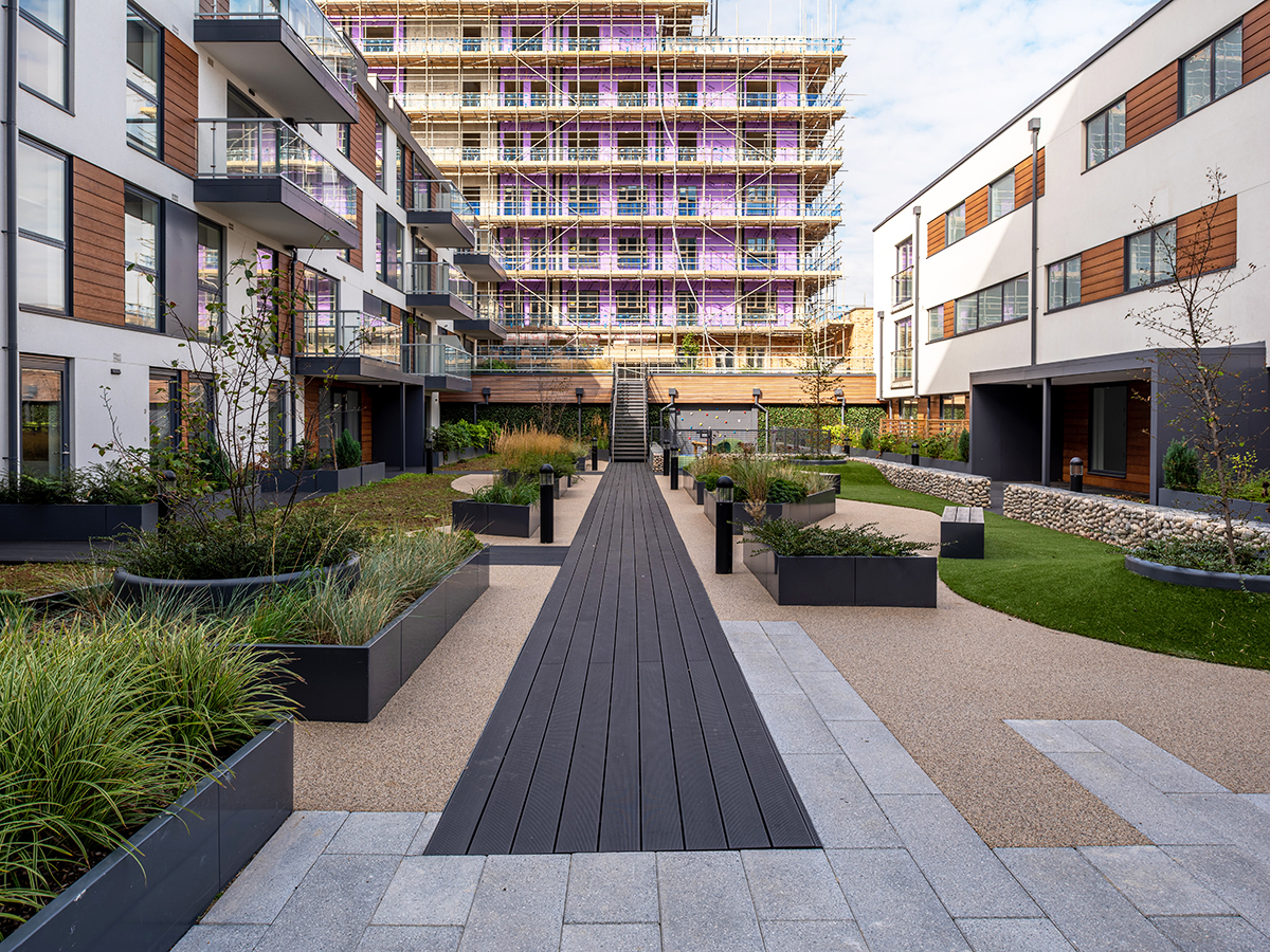 Roof park with central axis boardwalk along an array of sinuous shaped raised planters and sedum carpet which contain trees and grasses designed by Natural Dimensions