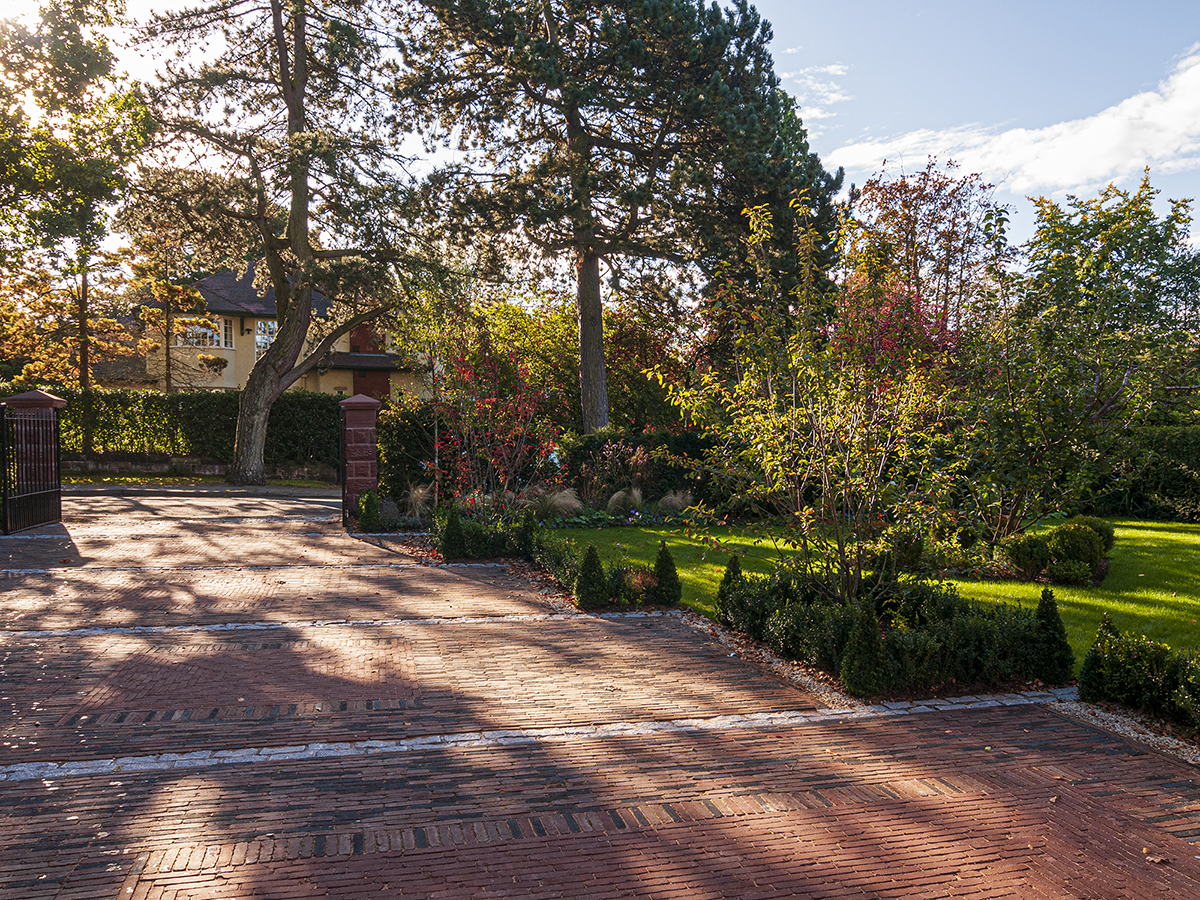 driveway with Belgian pavers and gate pillars box hedge and topiary and large pine trees