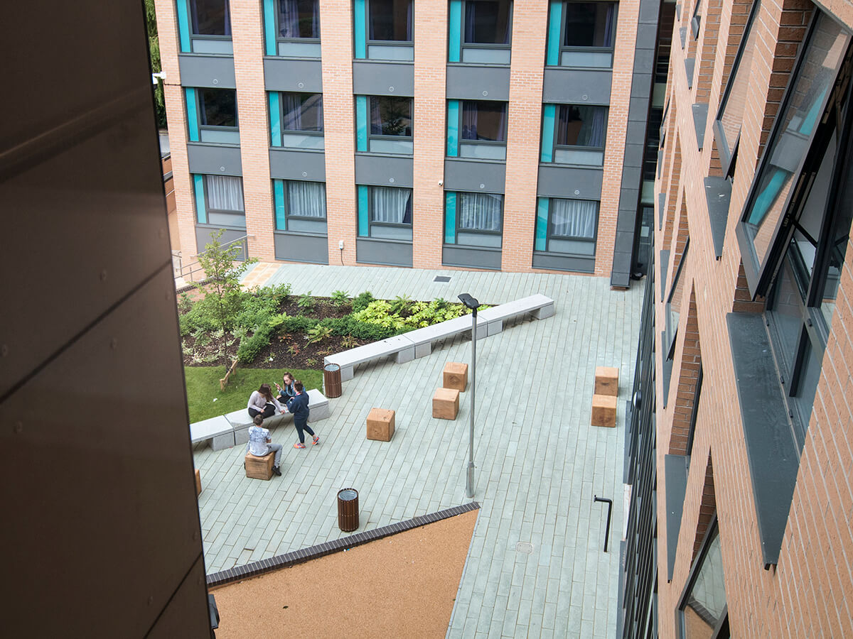 Natural Dimensions View of Fountians court Leeds Trinity University with linear granite bench, individual timber bale seats, plank paving carpinus betulus trees, fatsia japonica and buff resin bound gravel on ramp