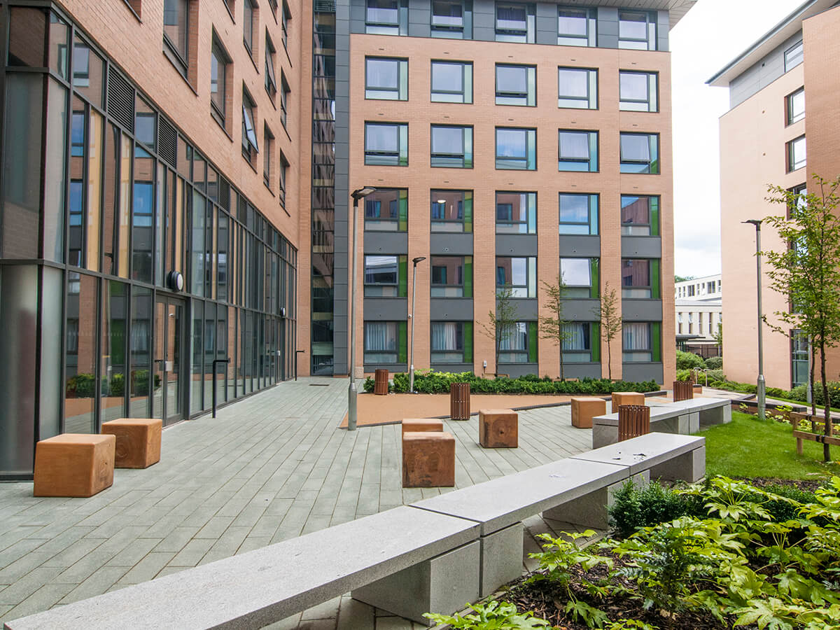 View of Fountians court Leeds Trinity University with linear granite bench, individual timber bale seats, plank paving carpinus betulus trees, fatsia and buff resin bound gravel on ramp
