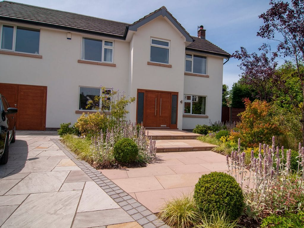 View of front garden designed by Natural Dimensions with steps rising to front door including Carex Evergold, Astrantia, verbena boniarensis , Heuchera, stachys and buxus balls