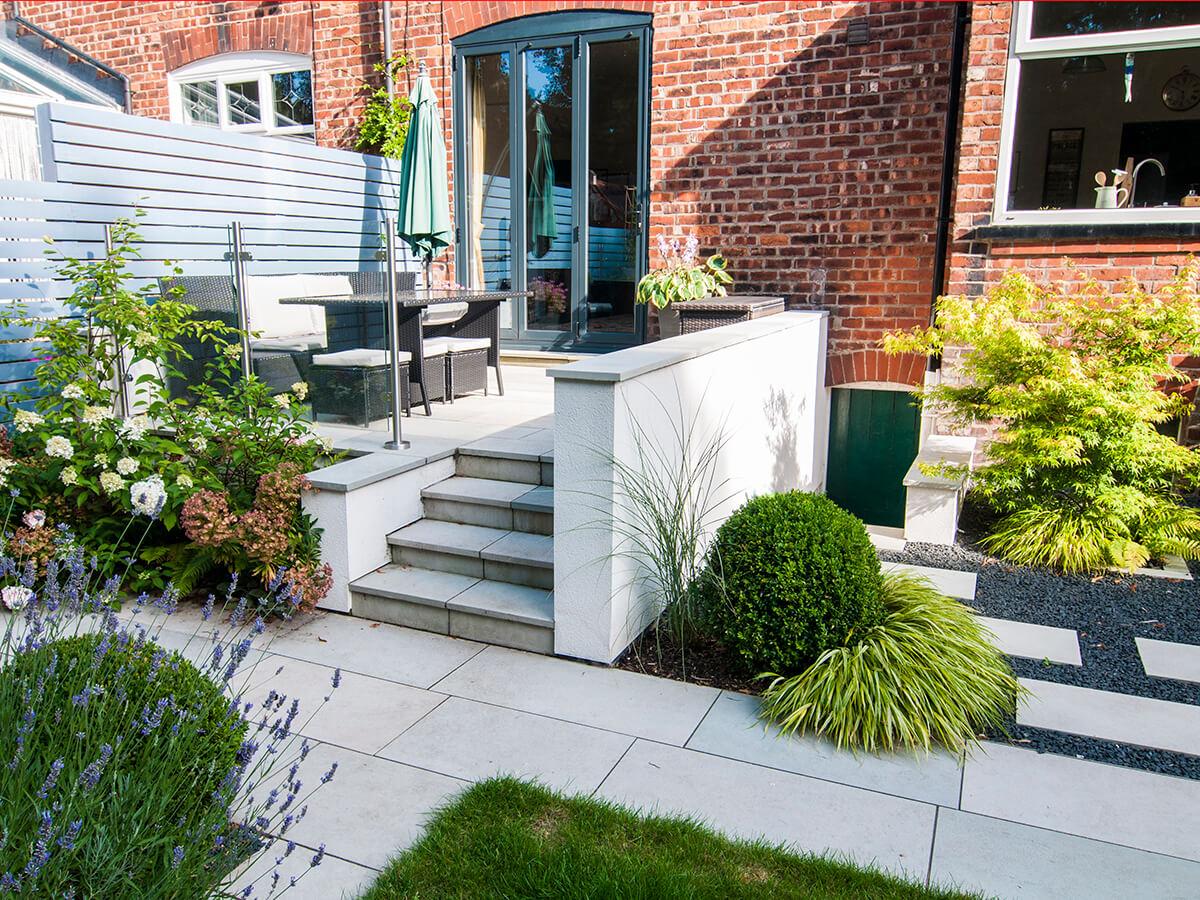 natural dimensions garden design, raised patio, black basalt stepping stones, topiary, hydrangea, miscanthus