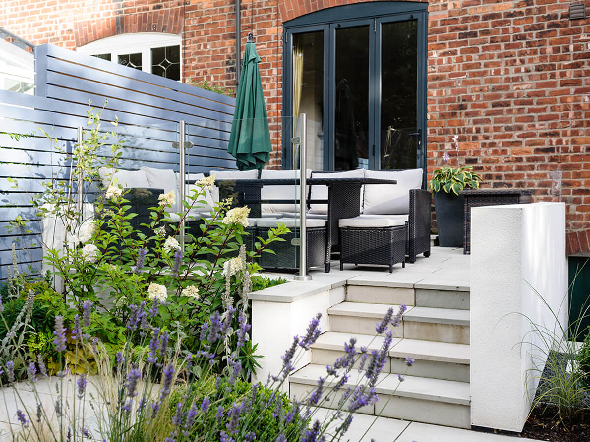 White rendered wall raised patio with rattan dining furniture and lavender, hosta and sun canopy with painted slatted fence