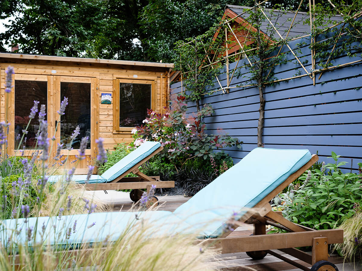 Pleached trees, sun loungers and garden office with juniper ash slatted fence