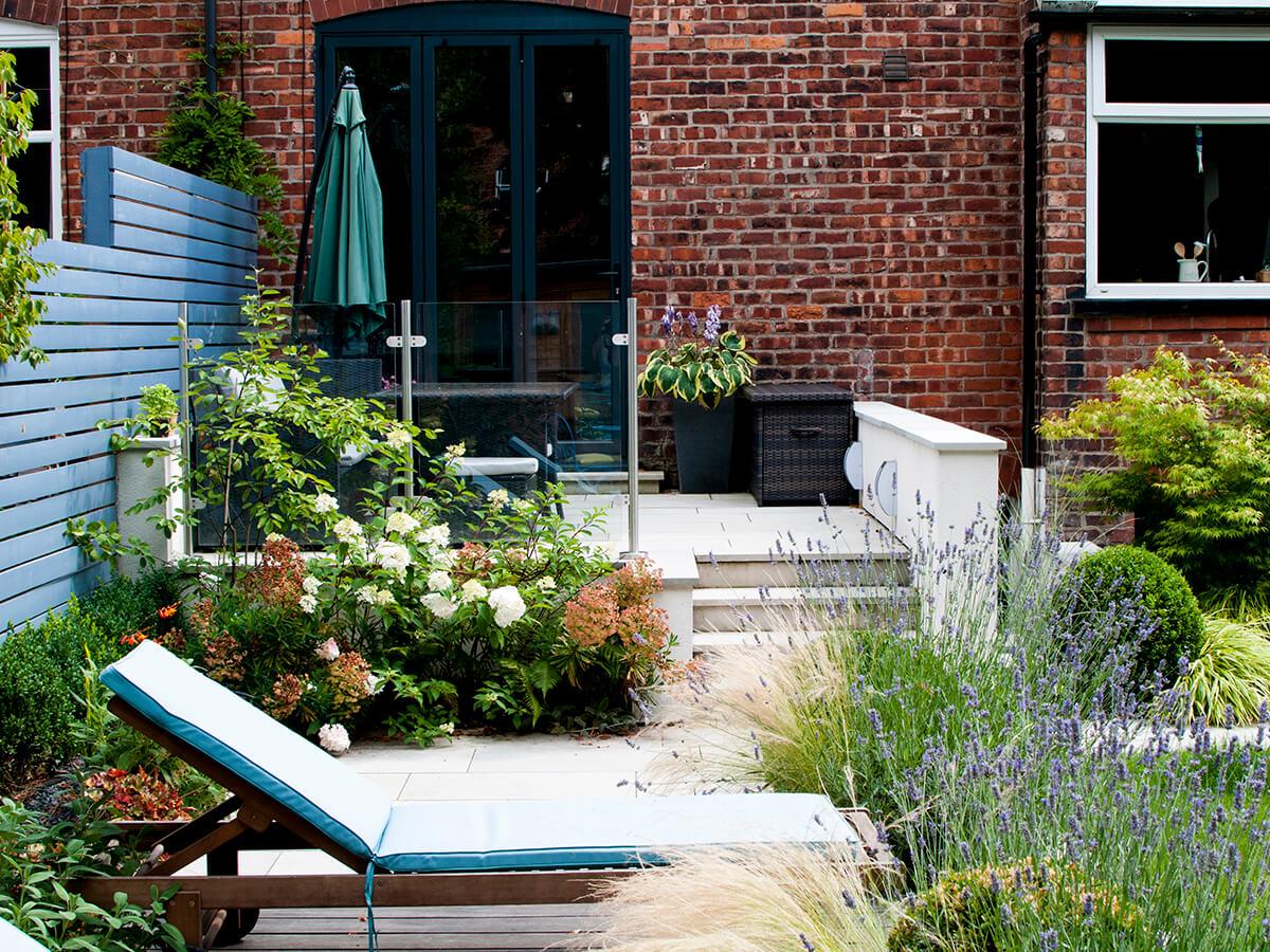 sun lounger, little greene painted slatted fence, lavender, pleached hornbeam, white rendered wall, natural dimensions garden design