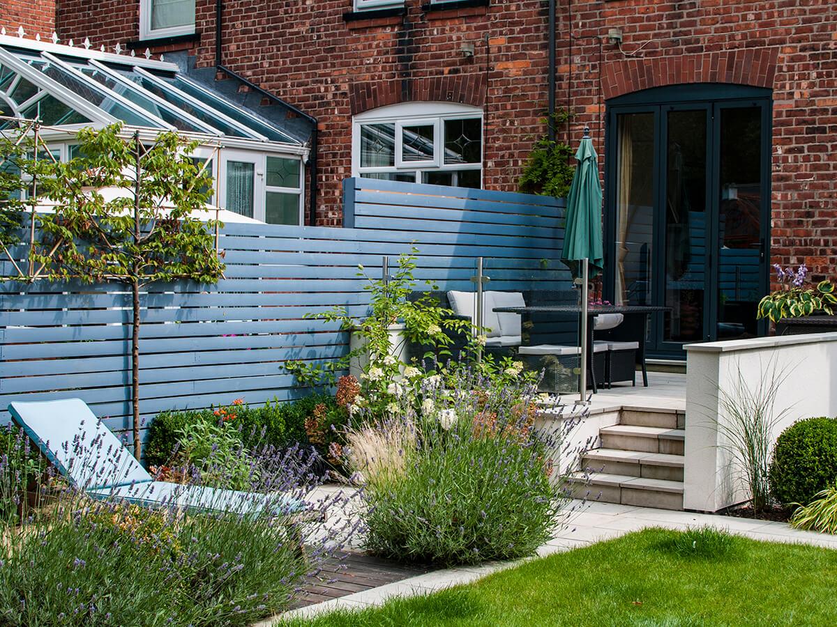 sun lounger, little greene painted slatted fence, lavender, pleached hornbeam, white render, natural dimensions garden design