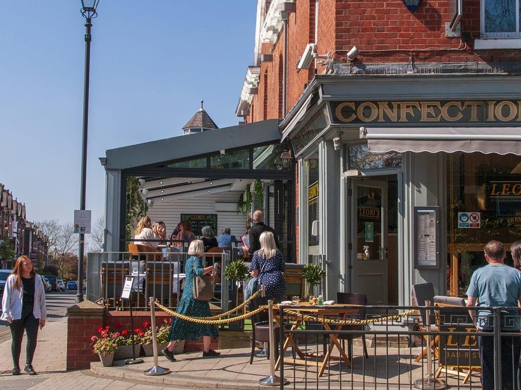 streetlife people drinking at Leoni's on outdoor seating street on Heaton Moor Road post lockdown